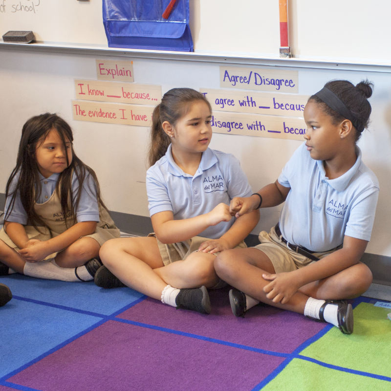 Alma scholars shaking hands in the classroom