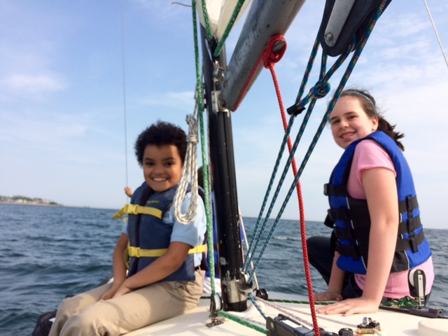 Alma del Mar scholars enjoy a sunny afternoon in a sailboat with instructors from the Community Boating Center.