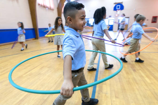 A young Alma scholar walks with a hula hoop around his waist in the gymnasium.