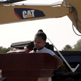 Young Black girl speaking in front of construction equipment