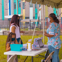 Alma staff member speaks with woman and child at Family Orientations