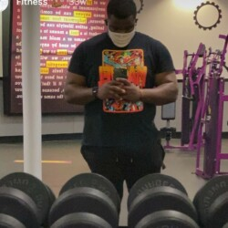 Samuel Francois poses in front of a mirror and sets of weights.