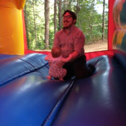 Adam Mercier kneeling in a bouncy house, playing with a young child.