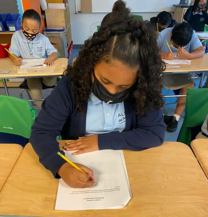 Elementary scholar sits at desk in third grade classroom while completing math problems in a packet.