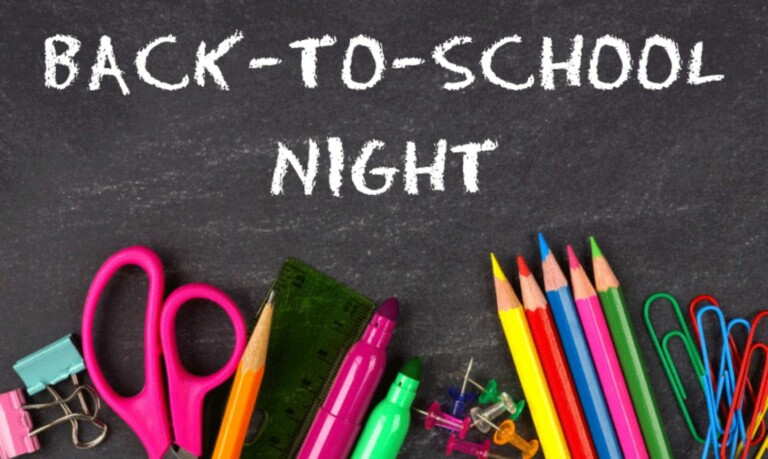 Back To School Night written in chalk on a chalkboard with colored pencils and markers below